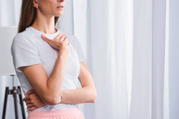 cropped image of worried woman with hand on chest in front of curtains at home - mão no peito imagens e fotografias de stock