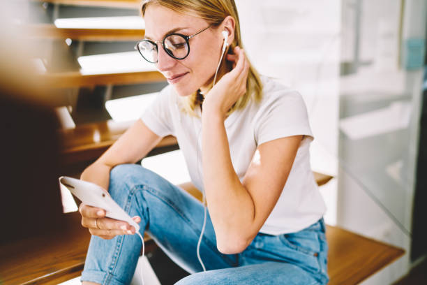 Cropped image of young attractive happy blonde woman in trendy eyeglasses spending leisure time at home with music. Charming positive hipster girl enjoying resting while listening to cool playlist stock photo