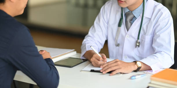 Cropped image of Young smart doctor diagnosing and giving advice to his patient while sitting together at the doctor working desk over comfortable clinic as background. stock photo