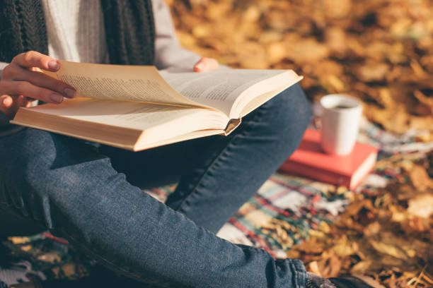 cropped image of young woman sitting on blanket, reading book and drinking coffee or tea in autumn garden - autumn stock pictures, royalty-free photos & images