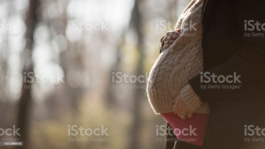 Cropped low angle view of a pregnant woman stock photo