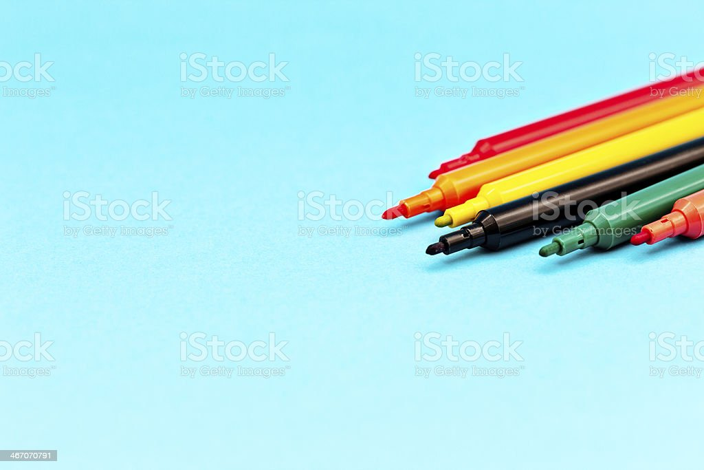 Cropped, multicolored, felt-tip pens on blue with copy space royalty-free stock photo