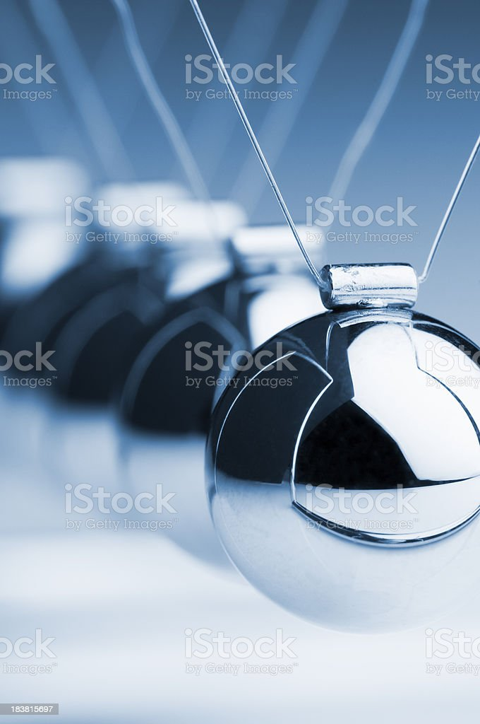 Cropped Newton's cradle with focus in foreground stock photo