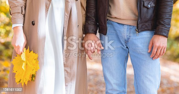 Panoramic cropped photo of couple holding hands and bunch of golden leaves, autumn romance, panorama