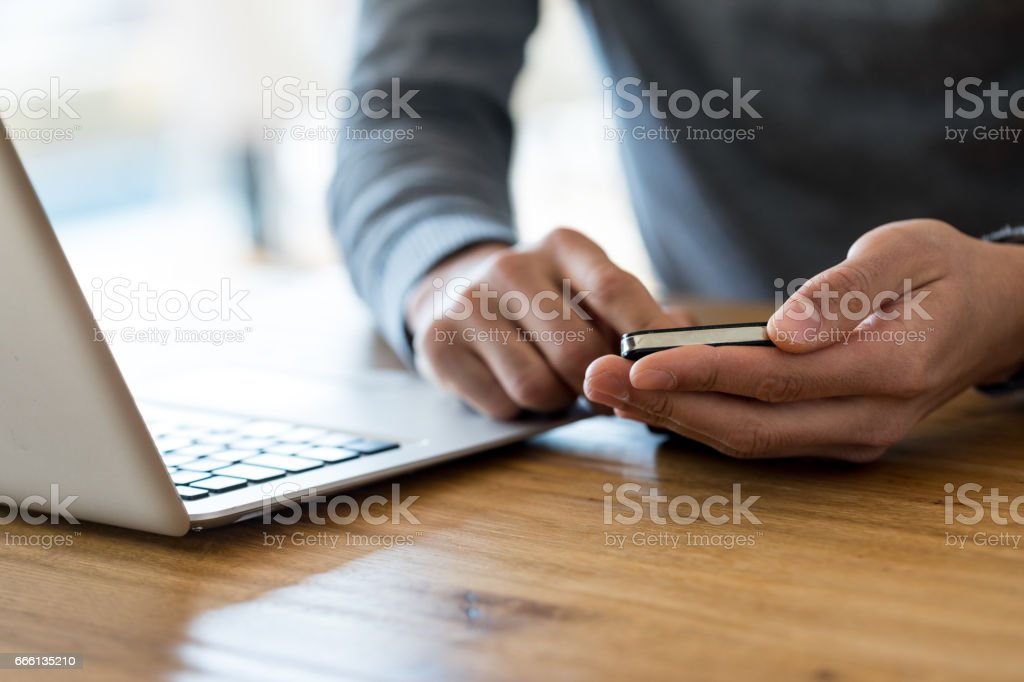 Cropped of man holding cell phone at working place stock photo
