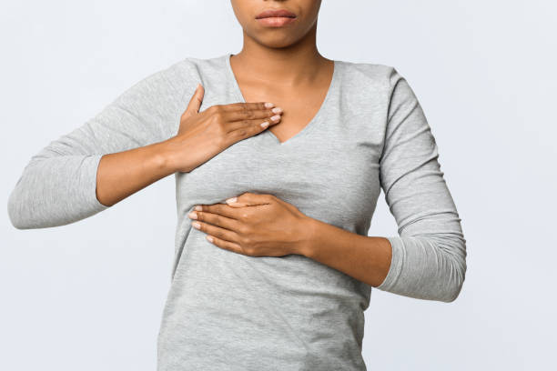 cropped of woman feeling menstrual cyclic breast pain, massaging her chest - cyclic stock pictures, royalty-free photos & images