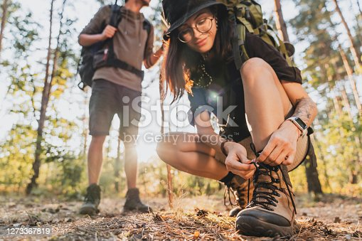 Cropped of woman tying hiking boot outdoors on trail in forest while travel with her boyfriend.