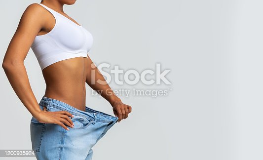 istock Cropped of young woman with too large jeans 1200935924