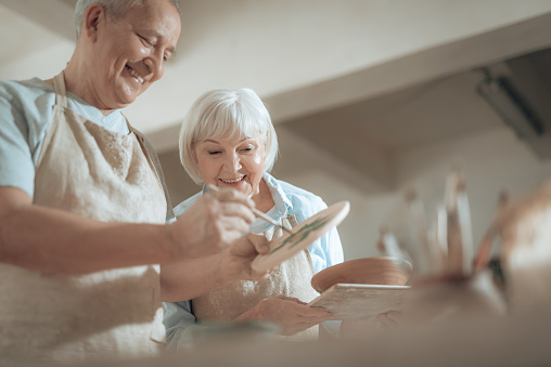 Cropped photo of elderly couple working in potter's studio