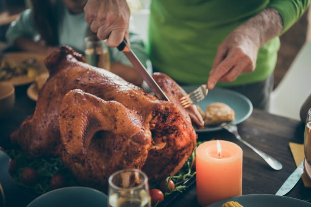 cropped photo of family feast roasted turkey on table grandfather hands cutting meat into slices hungry relatives waiting in living room indoors - thanksgiving turkey zdjęcia i obrazy z banku zdjęć