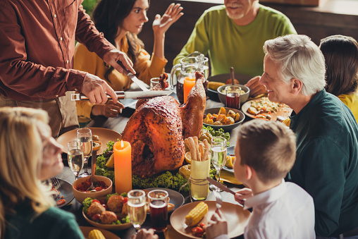 Cropped photo of family meeting, served table thanks giving dinner two knives slicing stuffed turkey meal living room indoors