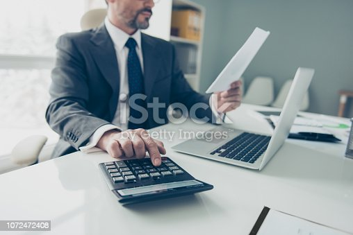 Cropped photo of handsome attractive good-looking good-wearing man in formalwear sit on chair armchair behind table in bright lite office presses button on calculator