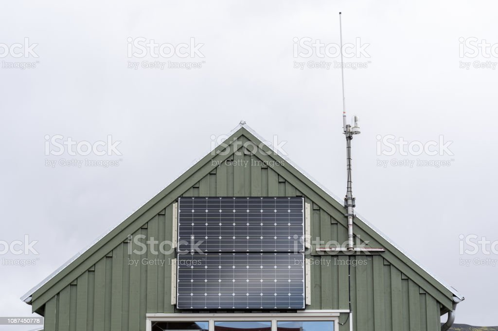 Cropped Photo Of Little Green House With Small Solar Panel At The