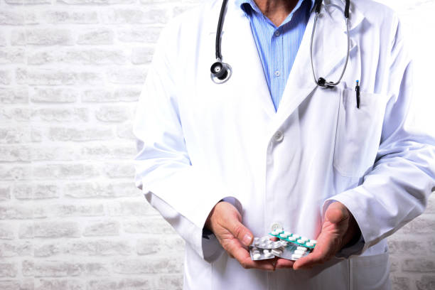 Cropped photo of Senior male doctor with pills in hands Cropped photo of doctor in white coat and stethoscope with hands full of various pills. The concept of medicine and pharmacy for the successful treatment of disease. Doctor giving you a pills anticoagulant stock pictures, royalty-free photos & images