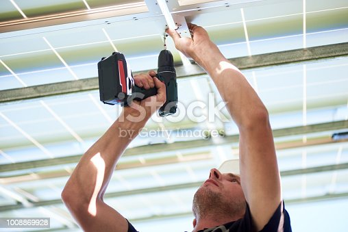 istock Cropped photo of worker using drill by solar panels mounting. 1008869928