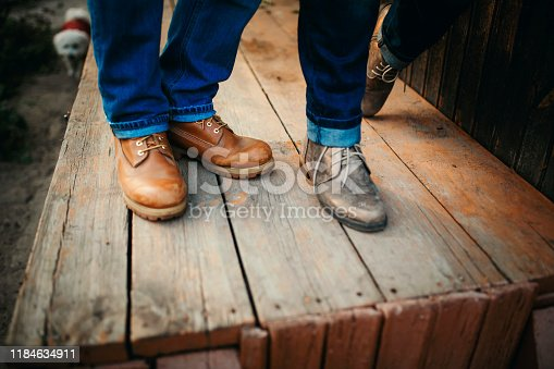 Cropped photo young legs in stylish shoes, married couple, husband and wife on a wooden bridge near lake. Rear view of couple standing on pier