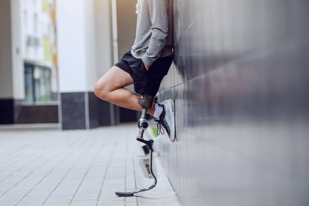 壁に立ち、ポケットに手をつないで人工脚を持つスポーツマンのトリミングされた画像。 - 四肢 ストックフォトと画像