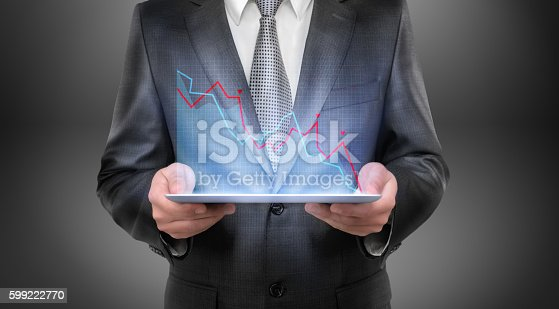 istock Cropped portrait of a businessman holding tablet with falling diagram 599222770