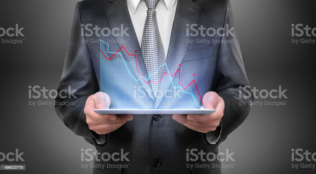 Cropped portrait of a businessman holding tablet with falling diagram stock photo
