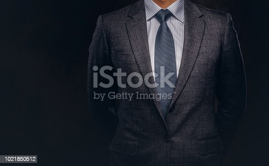 Cropped portrait of a successful businessman dressed in an elegant formal suit. Isolated on a dark background.