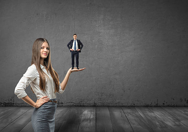 cropped portrait of big businesswoman holding small businessman on her - man dominating woman stock photos and pictures