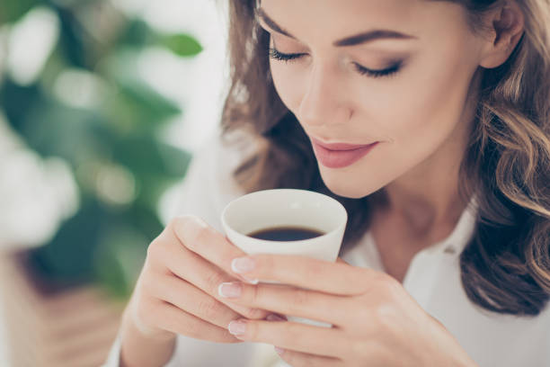 cropped portrait of charming, pretty, nice, cute, trendy woman enjoying smell of tasty coffee with close eyes having natural make up morning pleasure ritual at home, idyllic concept - annusare foto e immagini stock
