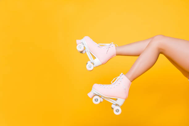 Cropped portrait of legs in pink vintage quad roller skates shoes isolated on yellow background, extreme balance concept, street outside urban lifestyle style, laser hair removal perfect skin stock photo