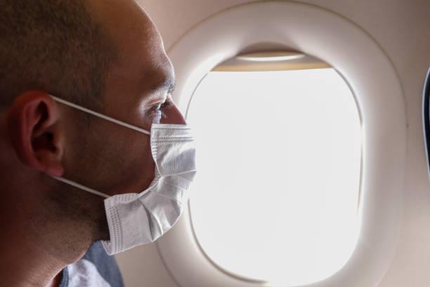 cropped portrait of man in respirator mask flying on a plane. - covid flight imagens e fotografias de stock