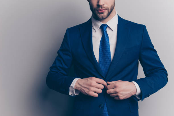 cropped portrait of stunning, fashionable, cool, virile, rich man with stubble, half face in blue suit fasten button on jacket with two arms, isolated on grey background, going for meeting, date - галстук стоковые фото и изображения