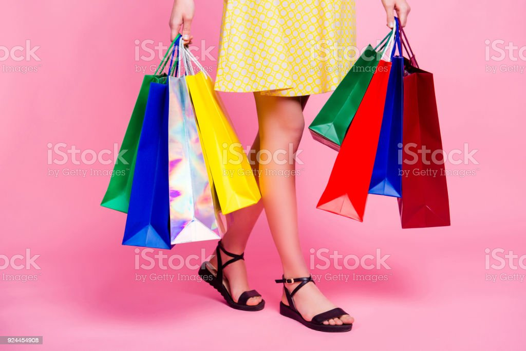 Cropped portrait of woman's slim sexy legs going from shopping having a lot of colorful bags in hands isolated on pink background, day of big sales stock photo