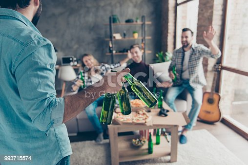 istock Cropped rear view of visitor bringing bottles with beer to his stylish, successful, attractive friends  who extremely happy, glad to see him with raised palm gesturing on blurred background 993715574