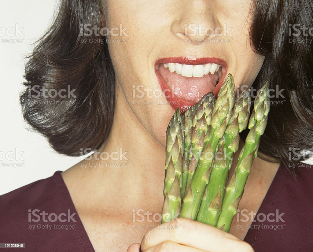 cropped section of female face biting asparagus royalty-free stock photo
