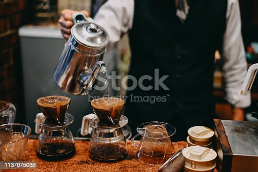 istock Cropped shot barista coffee maker Old man dripping a coffee on coffee pot with vintage tone. 1137075035