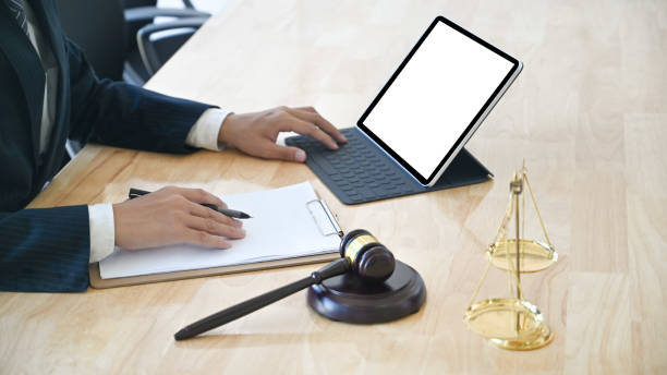 Cropped shot business lawyer working with paper and mockup tablet. stock photo
