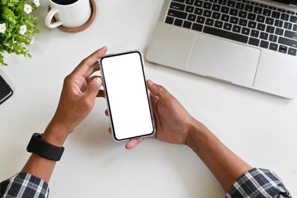 mano cortada con un teléfono inteligente de maqueta en el escritorio de oficina con trazado de recorte. - agarrar fotografías e imágenes de stock