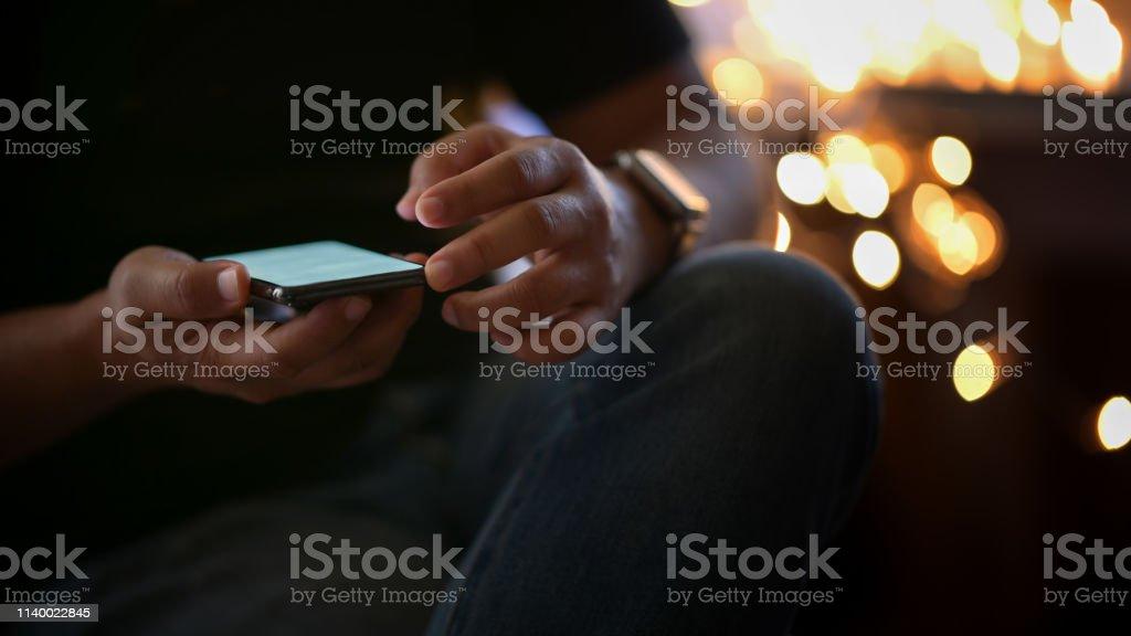Cropped shot man using mobile phone at walk street night.