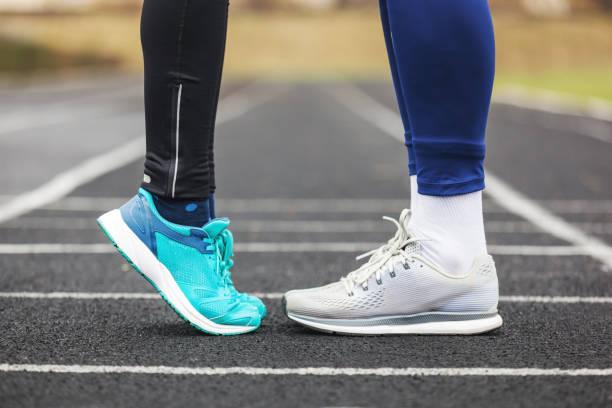 schuss von einem männlichen und weiblichen beine in laufschuhen nahe beieinander beschnitten. - neue sneaker stock-fotos und bilder