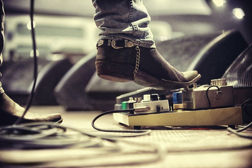 Cropped shot of a music artist's foot on a foot pedal. This concert was created for the sole purpose of this photo shoot, featuring 300 models and 3 live bands. All people in this shoot are model released.
