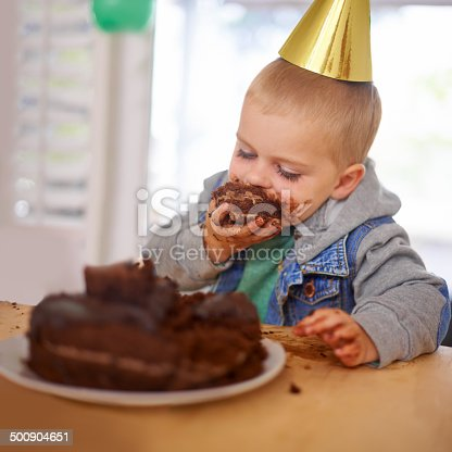 Cropped shot of a young boy eating his birthday cake before the party