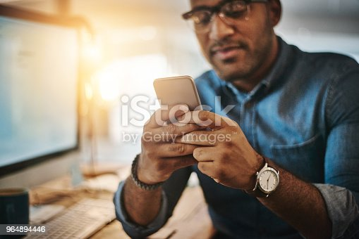 Cropped shot of a young businessman using a mobile phone during a late night at work