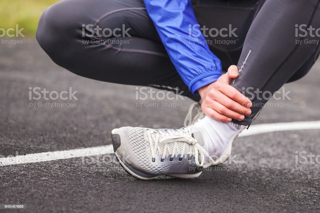 Cropped shot of a young man holding his ankle in pain sprain a foot. stock photo