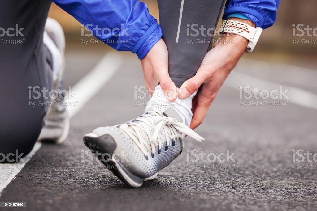 Aufnahme eines jungen Mannes mit seinem Knöchel in Schmerzen Verstauchung eines Fußes zugeschnitten. – Foto