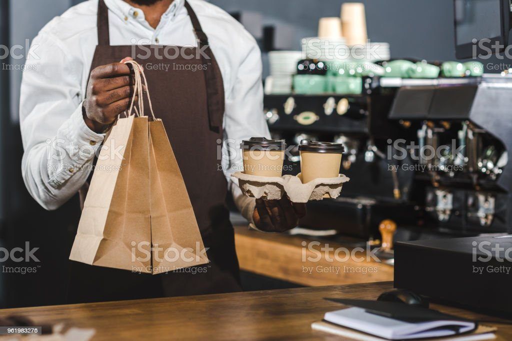cropped shot of african american barista holding disposable coffee cups and paper bags in cafe stock photo