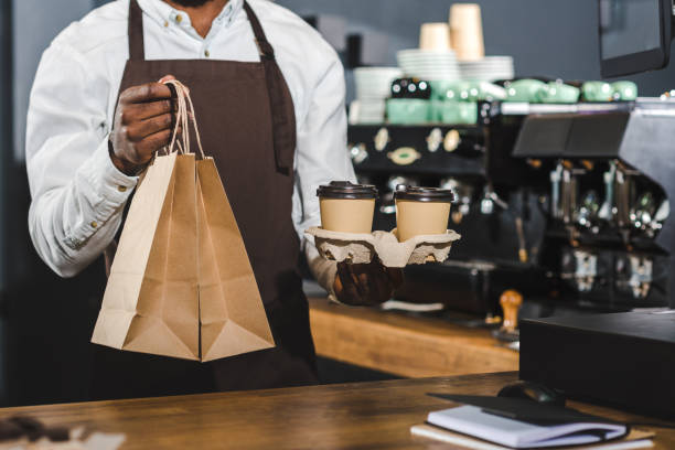 cropped shot of african american barista holding disposable coffee cups and paper bags in cafe cropped shot of african american barista holding disposable coffee cups and paper bags in cafe junk food stock pictures, royalty-free photos & images