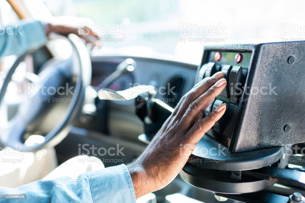 cropped shot of african american bus driver pushing buttons on panel at bus stock photo