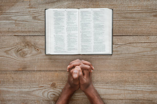 cropped shot of african american man praying with holy bible on rustic wooden table - african american church stock pictures, royalty-free photos & images