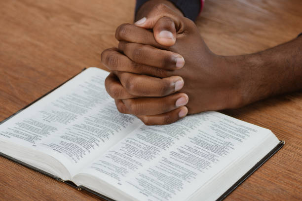 cropped shot of african american man praying with holy bible on wooden table - african american church stock pictures, royalty-free photos & images