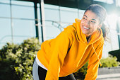 Cropped shot of an attractive African young lady smiling and resting after jogging with modern glass building behind