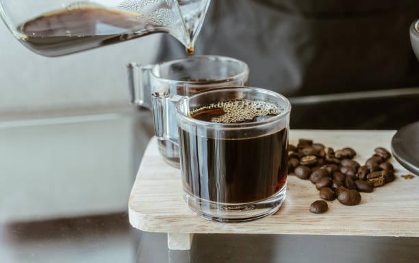 przycięte strzał barista wylewanie gorącej kawy po kroplówce w szklanej filiżance kawy. - coffee zdjęcia i obrazy z banku zdjęć