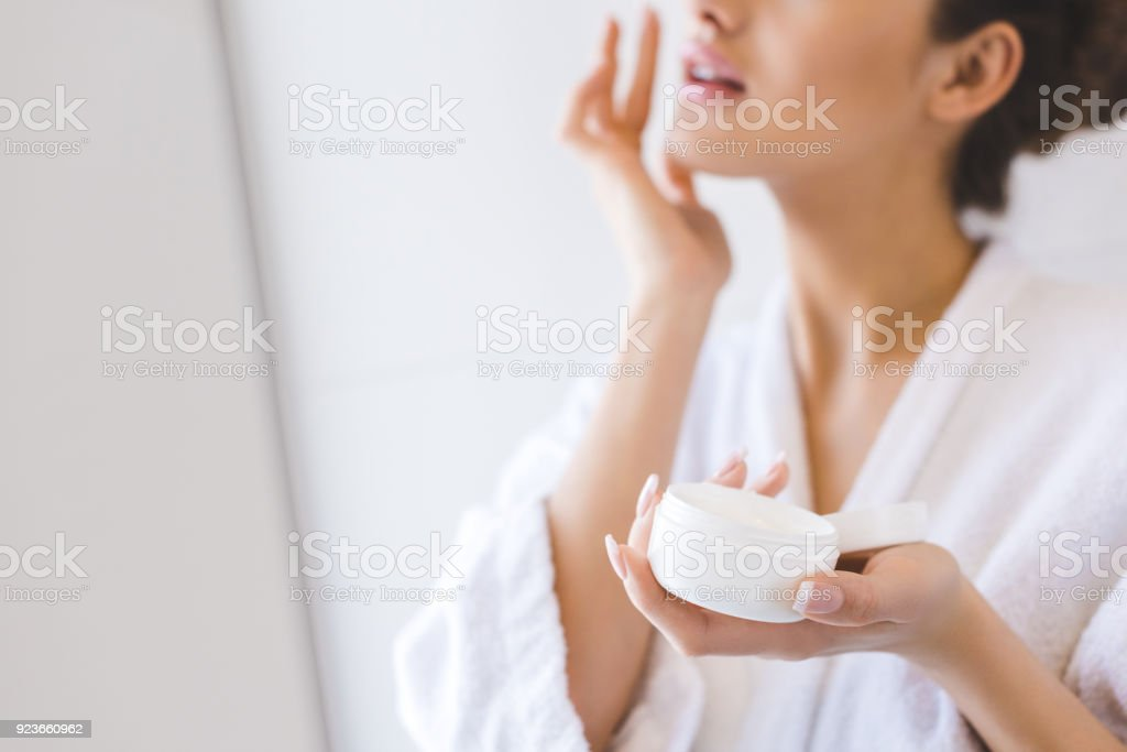 cropped shot of beautiful woman in bathrobe applying face cream stock photo